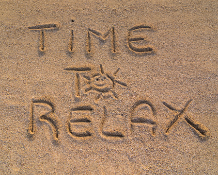 In the picture the words on the sand Time to relax