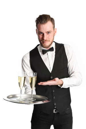 Young attractive waiter wearing a white shirt and black vest serving 2 glasses of champagne. White background.