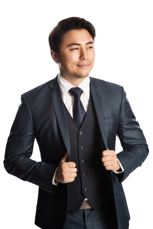 Handsome young entrepreneur with a smile standing against a white background wearing a blue suit, tie and vest.