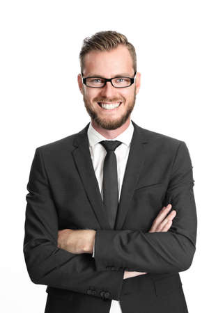 Photo pour A successful and happy executive businessman wearing glasses, black suit and tie, and a white collared shirt with his arms crossed standing against white background - image libre de droit