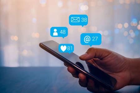 Photo pour Person hand using a mobile phone with social media marketing concept. - image libre de droit
