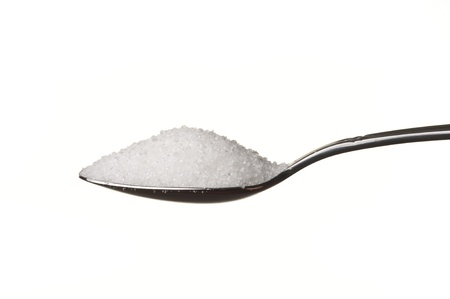 Sugar in a spoon isolated over white background