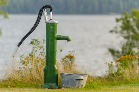 Old water pump in front of a lake in summertime