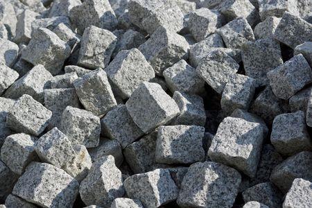 pile of grey cubical shaped granite cobblestones