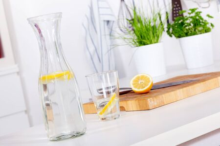 glass and carafe with refreshing lemonade on a kitchen counter