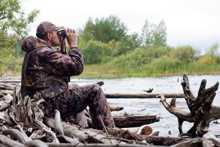 hunter looking through binoculars on the river