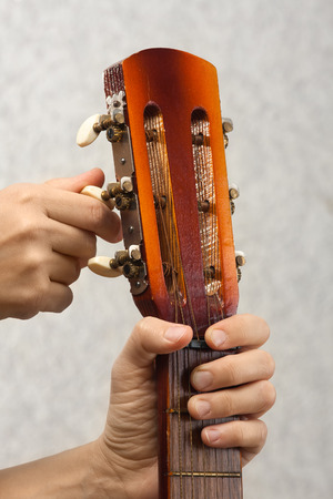 closeup of hands tuning acoustic guitar from headstock