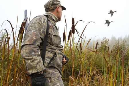 Photo pour a hunter with a shotgun on his shoulder follows the ducks with his eyes on a foggy morning - image libre de droit