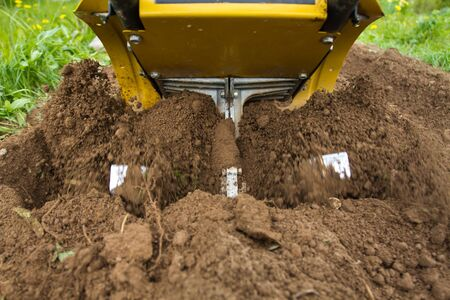 the cultivator loosens the soil in the garden, close up