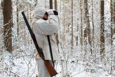 Photo pour a huntsman dressed in white camouflage stands in the northern forest and looks through binoculars - image libre de droit