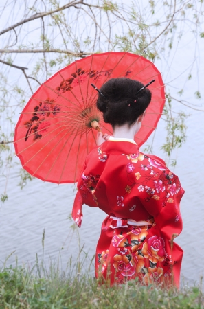 Geisha with red umbrella at the riverside  back view