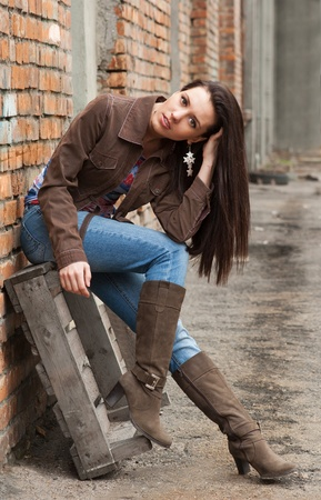 Girl in blue jeans sitting near the brick wall