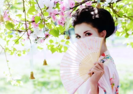 Asian style portrait of young woman with fan in the blooming garden