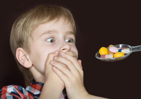 Photo pour Boy refusing to take medicine on a spoon - image libre de droit