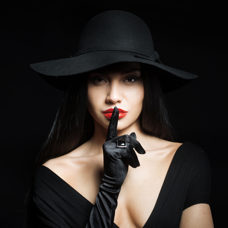Photo pour Woman in big black hat making a silence gesture, studio portrait, dark background - image libre de droit