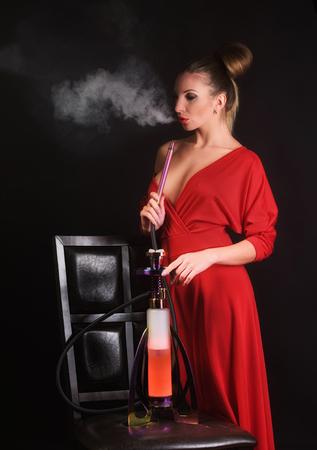 Sexy woman in red dress smoking hookah