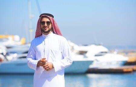 Photo pour Arabian man looking at the yacht harbor - image libre de droit