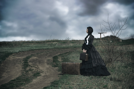 Foto de Outdoors portrait of a victorian lady in black sitting alone on the road with her luggage. - Imagen libre de derechos