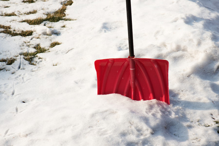 Red plastic shovel for snow removal. Winter concept.