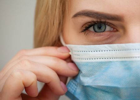 Photo pour Beautiful Women In A Medical Mask. Blond young woman wearing medical mask adjusting it with her hands close up - image libre de droit