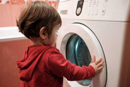 Photo pour Baby girl peeking into washing machine at home. Little Caucasian baby girl 1 year with washing machine. Home life childhood. - image libre de droit