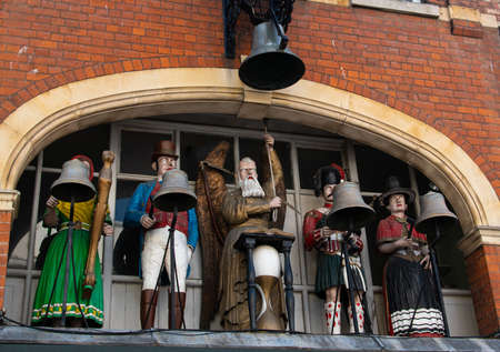 Gloucester, United Kingdom - September 08 2019:  The figures of the Baker's Clock built in 1904 with An Irishwoman, an Englishman, Old Father Time, a Scotsman and a Welshwoman above a bakery on Southgate Street