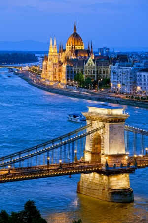 River view of Budapest at evening, illuminated Chain Bridge and Parliament Building.