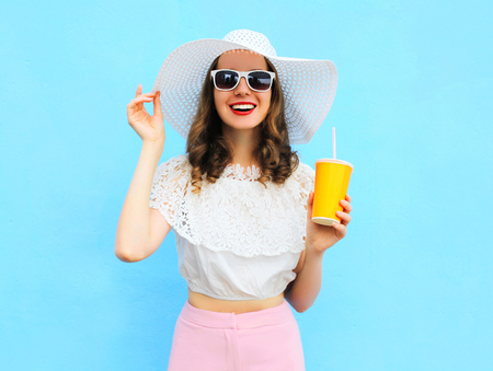 Photo pour Fashion pretty smiling woman in straw hat with cup fruit juice over colorful blue background - image libre de droit