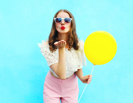 Photo for Pretty woman in sunglasses with air balloon sends an air kiss over colorful blue background - Royalty Free Image
