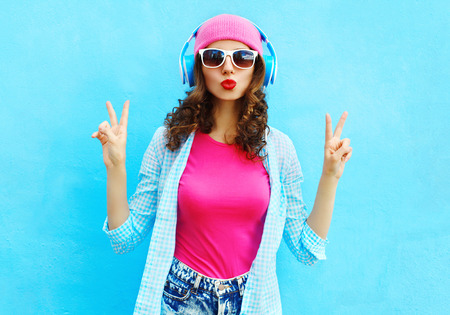 Photo pour Fashion pretty cool woman listens to music in headphones over colorful blue background - image libre de droit