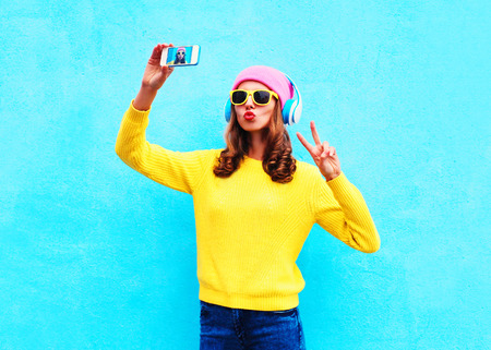 Photo for Fashion cool girl in headphones listening music taking photo makes self portrait on smartphone wearing a colorful clothes over blue background - Royalty Free Image