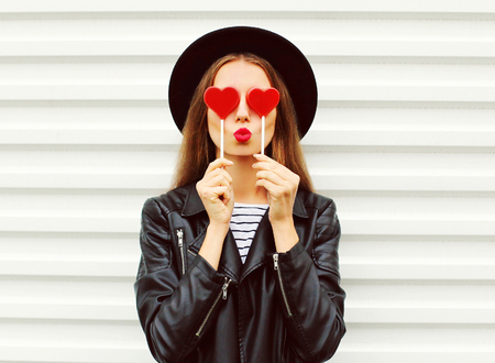 Foto de Fashion portrait pretty sweet young woman with red lips making air kiss with lollipop heart wearing black hat leather jacket over white background - Imagen libre de derechos