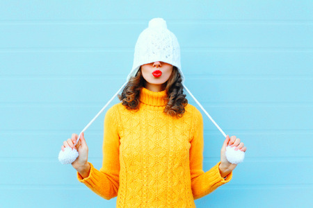 Foto de Happy cool girl blowing red lips makes air kiss wearing a knitted hat, yellow sweater over blue background - Imagen libre de derechos