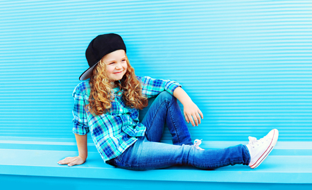 Street fashion concept - stylish kid little girl with curly hair on a blue background