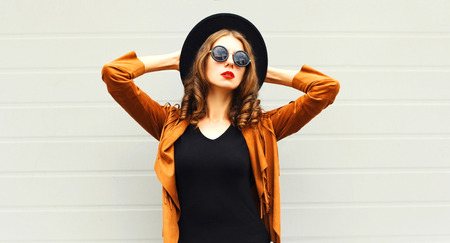 Foto per Fashion woman in black round hat, sunglasses, jacket on gray wall background - Immagine Royalty Free
