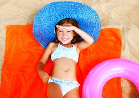 Photo pour Summer portrait little girl in bikini, straw hat lying sunbathing on sand beach - image libre de droit