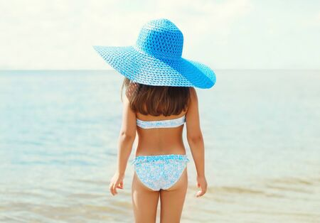 Photo pour Summer holidays, vacation concept - little girl in straw hat on beach over sea background - image libre de droit