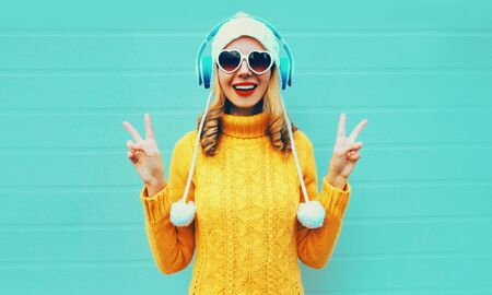 Photo pour Winter portrait happy smiling young woman in wireless headphones listening to music wearing yellow knitted sweater and white hat with pom pom, heart shaped sunglasses on blue wall background - image libre de droit
