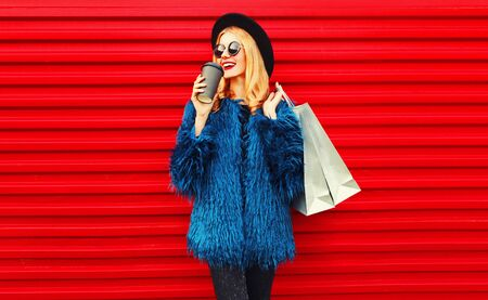 Photo for Portrait stylish smiling woman drinking coffee holding shopping bags wearing blue faux fur coat, black round hat and sunglasses posing over red wall background - Royalty Free Image