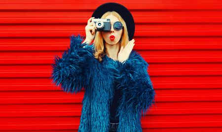 Photo pour Portrait cool surprised woman with retro camera taking picture wearing blue faux fur coat, round hat and sunglasses over colorful red wall background - image libre de droit