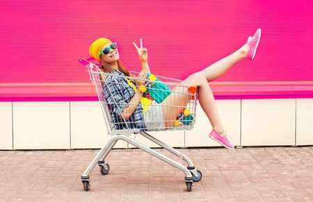 Photo pour cool young smiling woman having fun sitting in trolley cart with skateboard over colorful pink background - image libre de droit