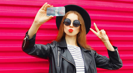 Photo for Attractive young woman taking selfie picture by phone blowing red lips sending sweet air kiss over colorful pink background - Royalty Free Image