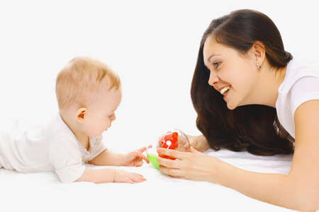 Photo pour Portrait of smiling mother and baby playing with toys over a white background - image libre de droit