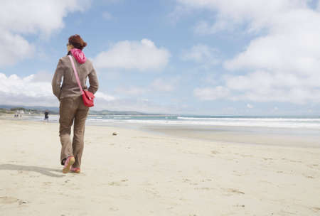 Fully dressed woman walking on a beach away from camera