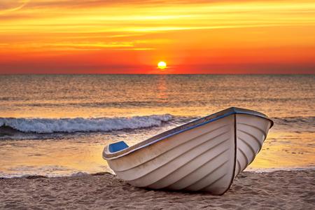 Photo pour Boat on the beach at sunrise time. - image libre de droit