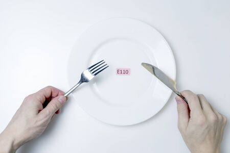 Photo for Photo Harmful food additives. Men's hands hold a knife and a fork. On the plate is a plate with the E-additive code. - Royalty Free Image