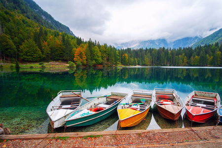 Photo for Lago di Fusine the mountain lake at boat and Mangart mountain in the background in north Italy alps, Europe - Royalty Free Image