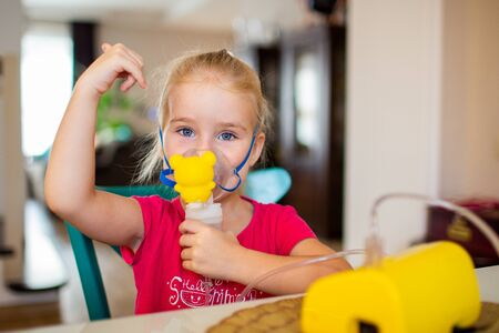 Photo pour Little girl with allergic asthma using inhaler and showing OK. Looking at camera. Girl inhales medicine through a nebulizer mask. Treatment of the respiratory tract. Safe treatment for influenza virus - image libre de droit