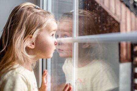 Foto de Little adorable blonde toddler girl looking through a window with rain drops on it. Close up portrait - Imagen libre de derechos