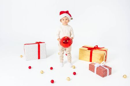 Foto de Little boy standing between gifts and holding big red Christmas ball in hands. Isolated on white background. - Imagen libre de derechos